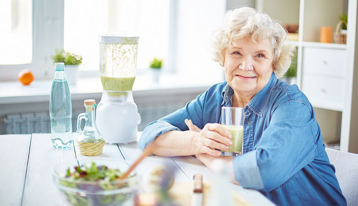 senhora idosa feliz toma suco verde sentada na mesa